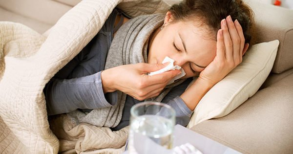 donna distesa con raffreddore che sorregge la testa