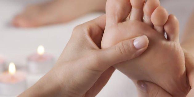 mano di riflessologa che tratta un piede